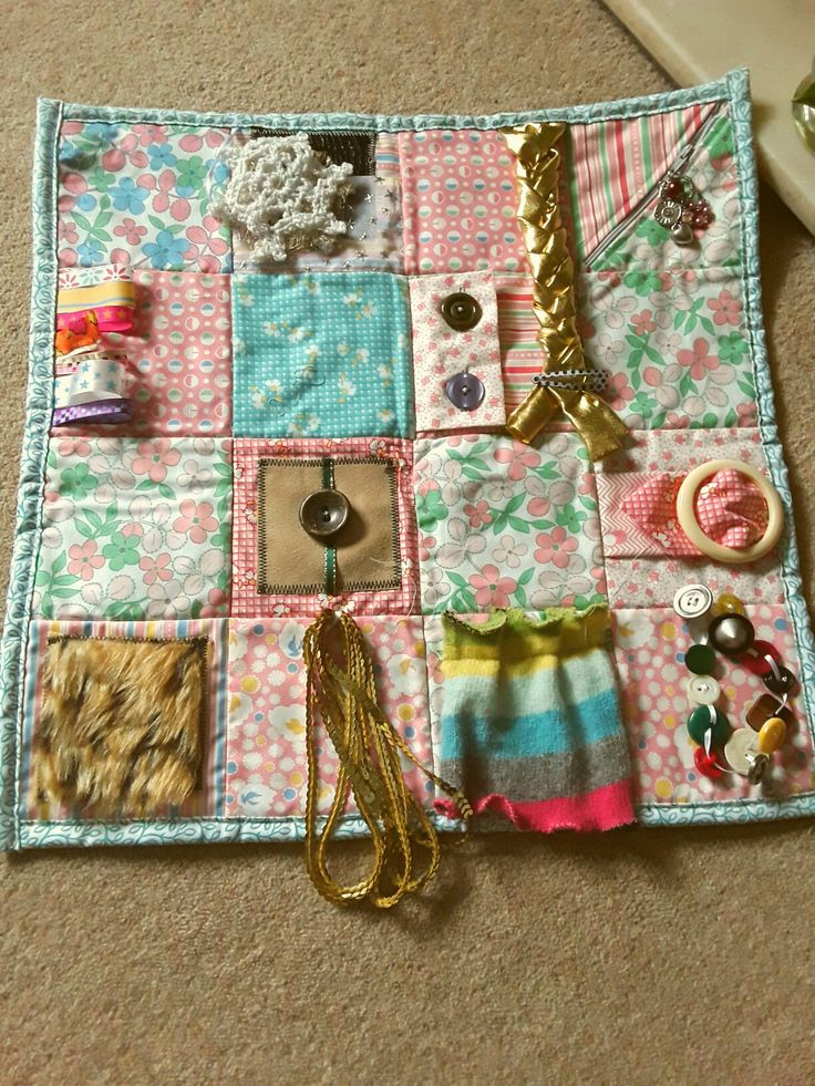 Dementia friendly activity mat.  This is backed with fleece fabric that will be easier to keep on a person's knee. Measures  about 20″ square.  Lots of textures, and things to open, close, operate or just feel. Also known as fidget quilt, twiddle quilt. A distraction for people with Alzheimers or living with dementia.Richelle Verootis