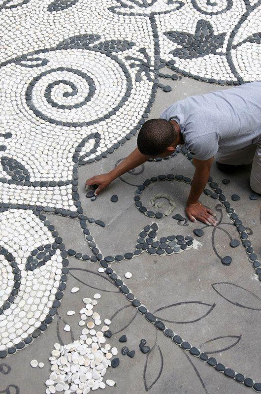 Wunderschöne Mosaik Idee für den Garten aus weißen und grauen Steinen.