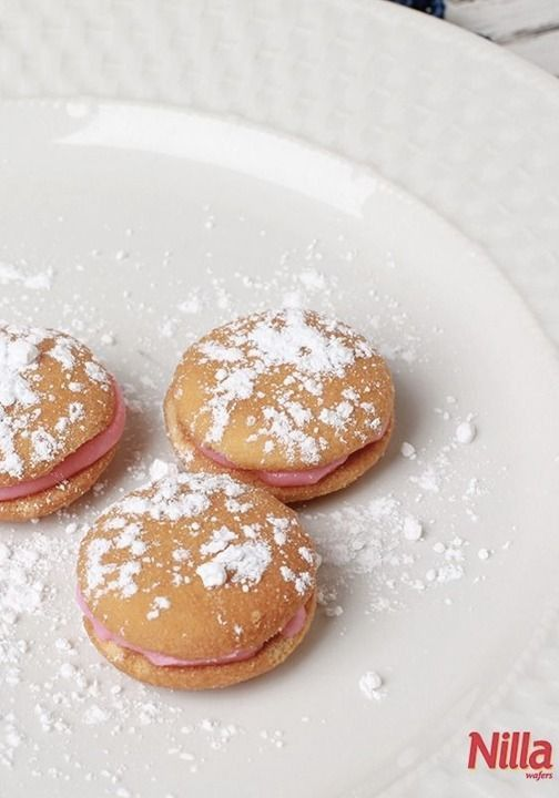 Powdered sugar and pink frosting on a Nilla Wafer make for a cute dessert that is simple and perfect to bring to a party! Make this for a simple baby shower dish!