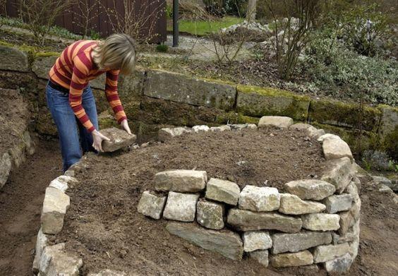 Hobby-Gärtnerin baut Rahmen aus Steinen für eine Kräuterschnecke.