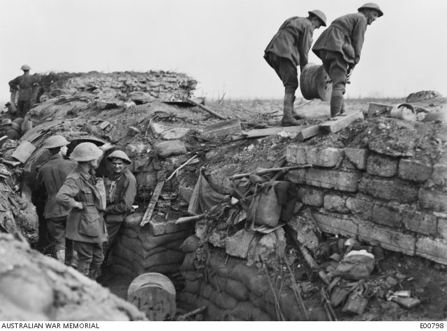 Australian Signal Engineers, with a reel of cable, leaving a Signal Office on Westhoek Ridge, in the Ypres Sector, to lay a surface telephone line to a forward unit, during the battle of Zonnebeke. Buried cable routes were mainly...