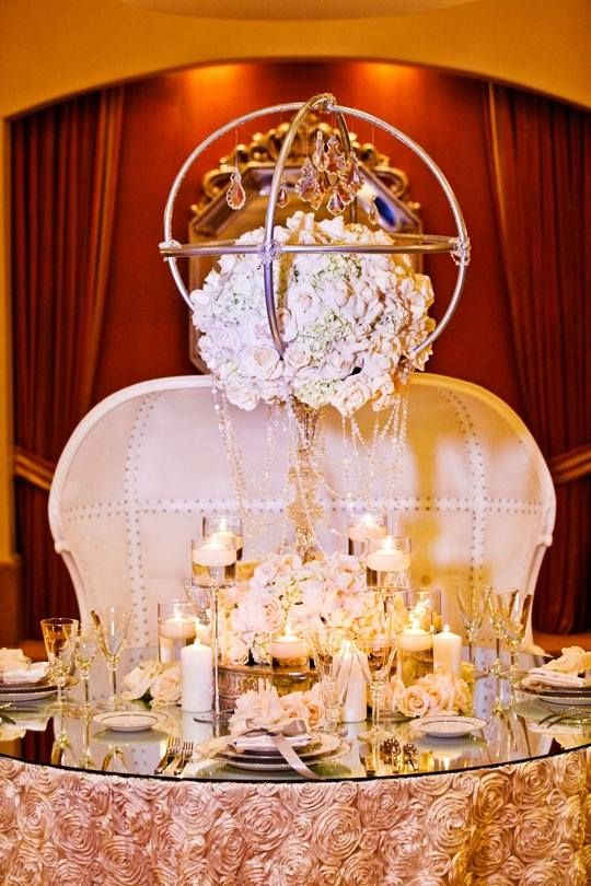 Couture wedding table with elegant white bench, large floral arrangement & lots of candles.