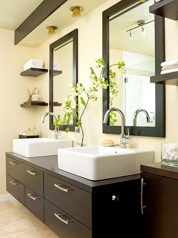 The floating vanity is part of the room's design illusion: to make the space feel bigger than it really is. Sleek, stained maple cabinets form the vanity base. Sculptural white vessel sinks with curved, contemporary faucets top it off.