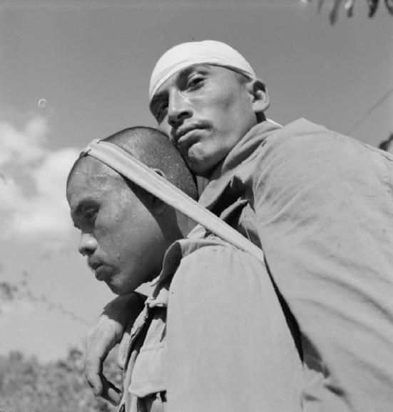 India 1944: A Gurkha soldier transporting a wounded man on his back through the jungle by Cecil Beaton