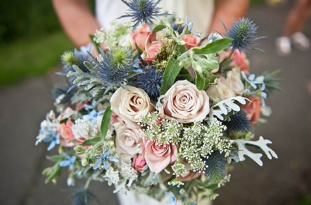 Blue Thistle, Queen Annes Lace, Dusty Miller, Tweedia, Light Pink/Cream Rose, and Peach/Pink Spray Roses.