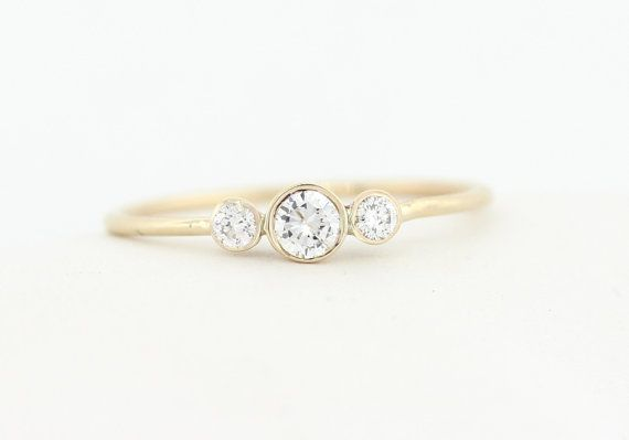 Hand made dainty gold three round brilliant cut diamond engagement ring available in yellow, white, and rose 14K gold.  The center diamond is a
