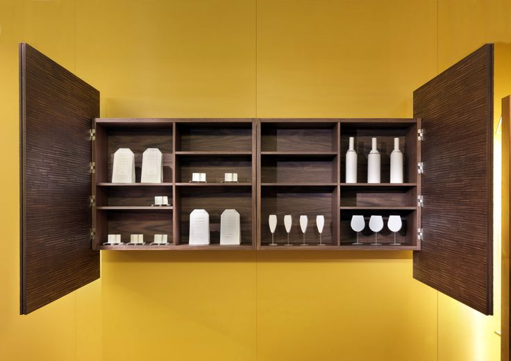 The wall cupboards have large hinged doors or doors with automated systems and open interior compartments where to store different objects.