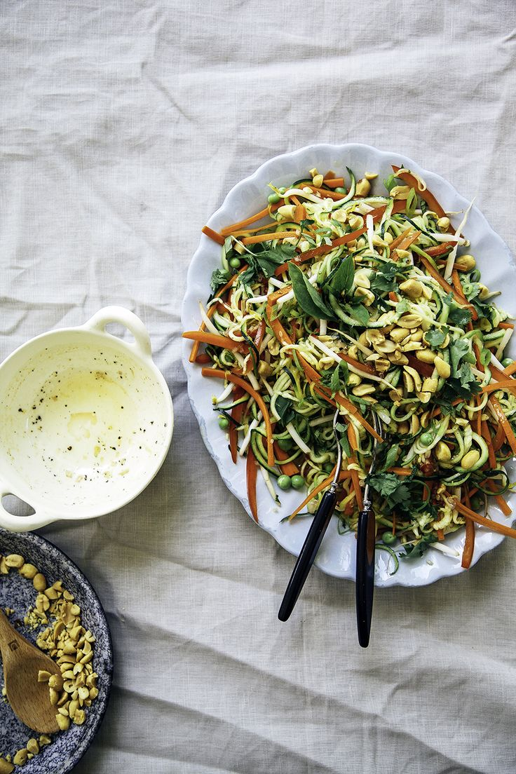 RAW PAD THAI SALAD ~ 1 T. minced shallot...2 t. minced chili...2 T. fresh lime juice...1 T. agave nectar (or other liquid sweetener)...1 t. gluten-free tamari... 2 T. veg. oil - SALAD – 2 large zucchini, ends trimmed... salt...1 carrot, peeled...1 red bell pepper, seeded...2 handsful bean sprouts...1/2 c. shelled fresh peas...handful fresh cilantro, rough chopped...2 sprigs Thai basil, leaves chopped...2 scallions, sliced...1/3 c. roasted, salted peanuts, chopped
