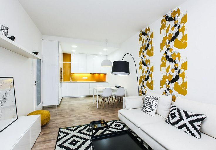 Dominantním prvkem obývací kuchyně je tapeta s výraznou okrovou a černou barvou.
