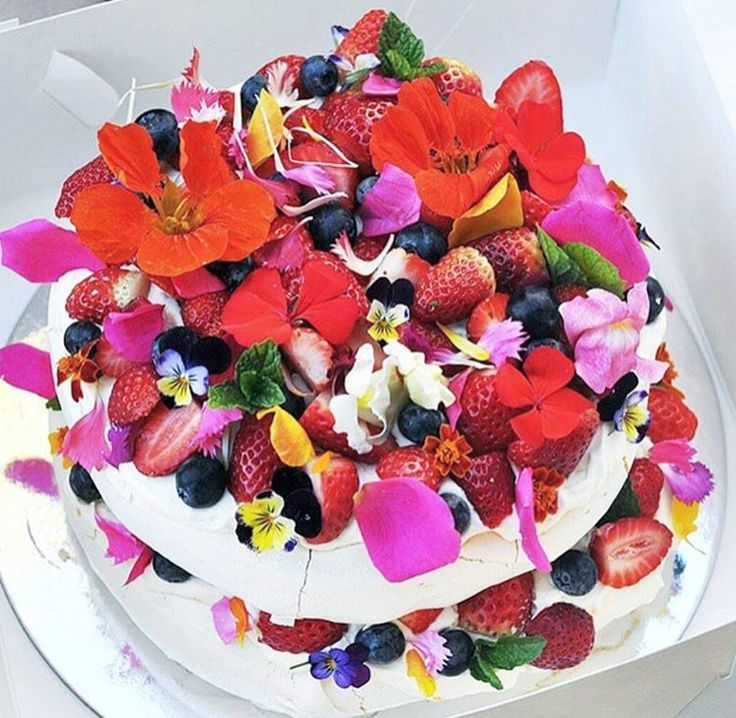 Summer pavlova decorated with berries and flower petals