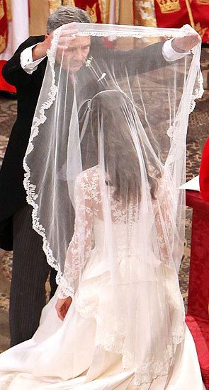 Mr. Middleton gently placing back the veil blusher on his daughter, Katherine the soon to be Duchess of Cambridge.