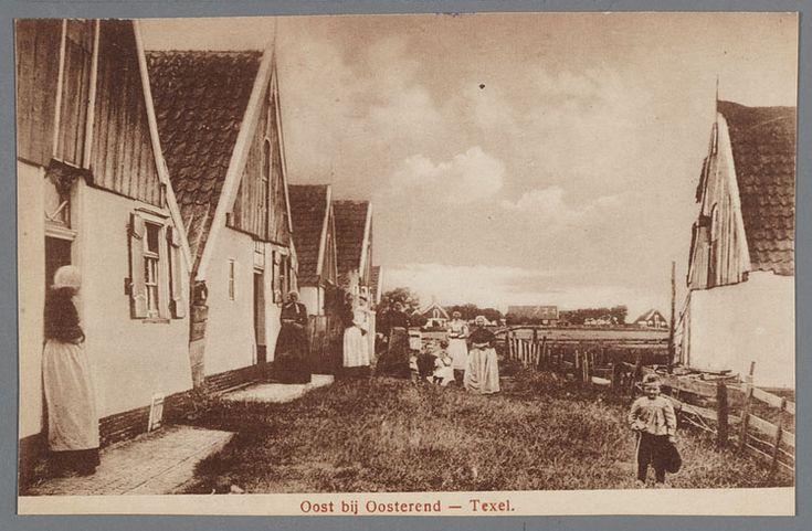 Oost bij Oosterend - Texel. Woonbuurt Zevenhuizen Vrouwen en kinderen in dracht poseren op een aflopend erf tussen huizen met houten topgevels. Rechts een houten hek als erfscheiding. 1900-1920 #NoordHolland #Texel