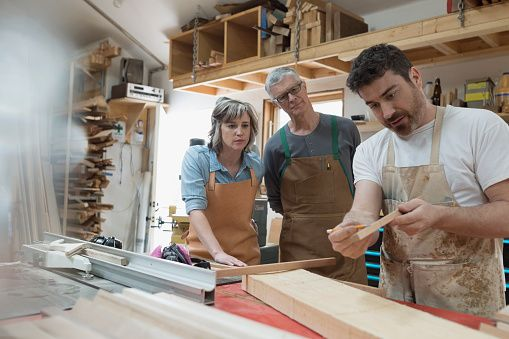 Carpenters examining wood piece in workshop