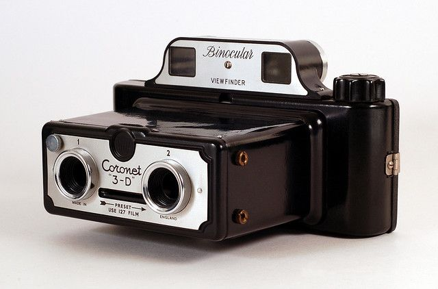 The Coronet 3-D is a stereo camera that was manufactured in England c1954. It's made of Bakelite and takes 127 film. The knob to the upper left of lens #1 allows that lens to be blocked in order to take single pictures (as opposed to stereo pairs).