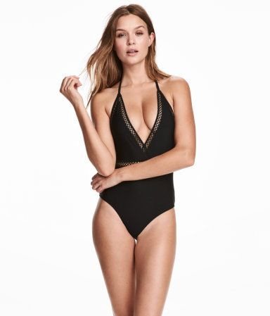 Black. Fully lined swimsuit with a wrapover V-neck at front, graphic lace details, and ties at back of neck.