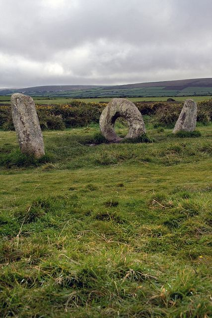 "Men-an-Tol, near Pendeen: the Mên-an-Tol (also 'Men an Toll') is a small formation of standing stones near the Madron–Morvah road.  'Mên-an-Tol' (Cornish) means ""the hole stone"". It consists of three upright granite stones: a round stone with its middle holed out and two small standing stones to each side. It is one of the best-known megalithic structures in Britain (photo taken 9 October 2012)"