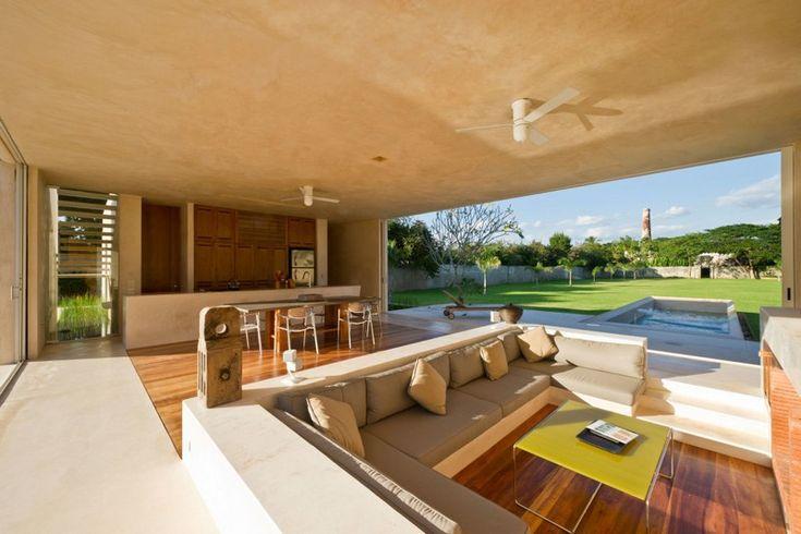 cuisine ouverte sur salon avec canapé énorme et ventilateurs plafond