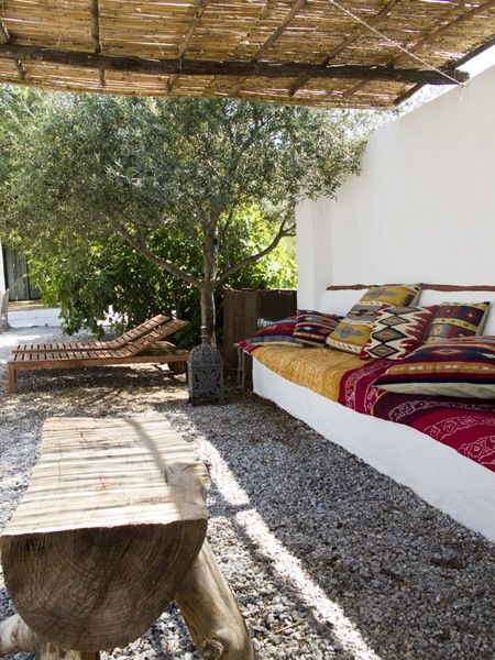 Amazing outdoor lounge space with built in bench covered in global fabrics and that amazing raw wood table.