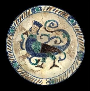 Dish. Made of blue, green, manganese-purple glazed and incised pottery. Laqabi ware. Islamic. Maybe 12th century, maybe 8th-9th.