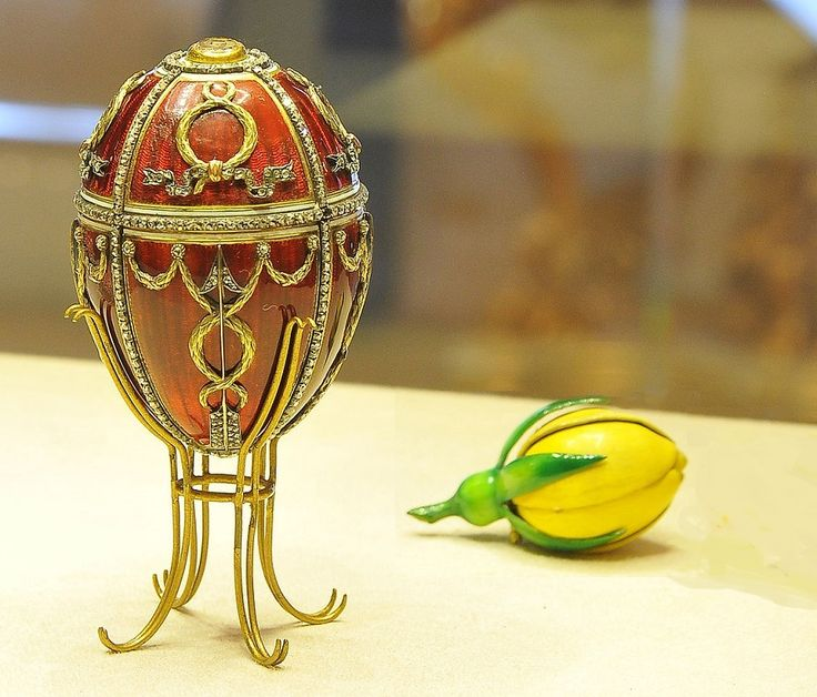 NEOCLASSICAL ROSEBUD EASTER EGG (11th Imperial Easter Egg)  c.1895   Russian; by Michael Perkhin  bright red, strawberry transparent enamel on a guilloche background, bright yellow enamel, 2 lg. flat diamonds, sm. diamonds, rubies, cabochon ruby pendant, ivory plate, yellow gold  1st Fabergé Egg given to Alexandra Feodorovna; decorated with diamond arrows, gold garlands & wreaths  Surprise: sm gold crown, w/diamonds & rubies; cabochon ruby pendant (Lost) Acquired by Viktor Vekselberg in 2004…