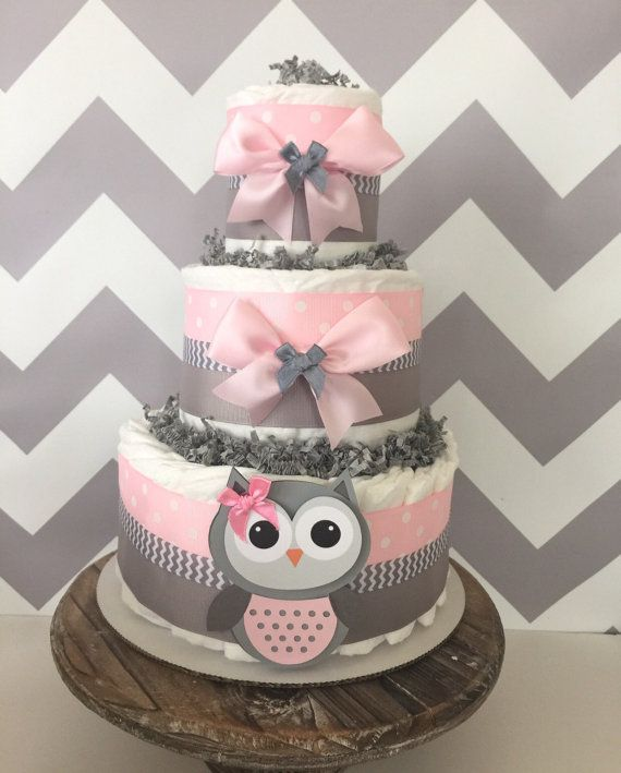 Owl Baby Shower Diaper Cake designed in a popular pink and grey color scheme and perfect for the centerpiece at the upcoming themed party!  This stylish Owl 3 Tier Diaper Cake is constructed with 3 layers of brand name disposable diapers, quality matching ribbons and bows and adorable handcrafted Owl card stock cutout!  OWL DIAPER CAKE INCLUDES: ------------------------------------------------------------------------------------------------ 40-45 Pampers Swaddlers Disposable Diapers in Size…