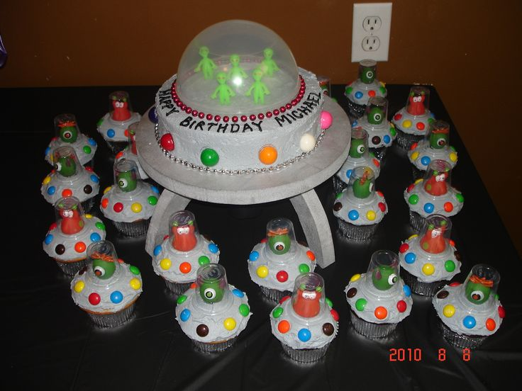 "Alien Invasion!!! - This creation was done for my son's 5th birthday party.  My husband made the cake board/ufo platform so when I made an 8"" single layer cake to sit on top of it, the whole thing would look like a UFO (a.k.a. the mothership).  I then trimmed the bottom of the cake with silver Mardi Gras beads as well as red beads around the plastic dome.  Large ""lights"" around the UFO cake are gumball.  The alien men inside are from a party supply store. All of the cupcakes are topped with…"