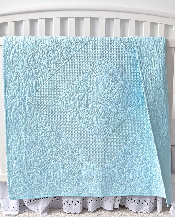 This elegant whole cloth baby quilt was made with blue Kona Cotton. It has beautiful longarm quilting with feather designs, detailed stippling