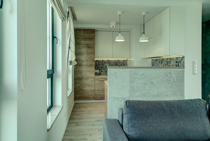 Kuchnia w minimalistycznym stylu pasująca do surowego, wręcz betonowego wnętrza. Drewno, biel i beton dominują w tej aranżacji wnętrz.
