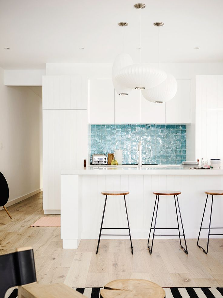 White kitchen with blue tiled backsplash and modern chandelier