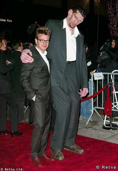 "Matthew McGrory was a  7' 6"" actor.  He had a pleasant deep voice and appeared in movies and TV shows, notably Big Fish, Men in Black II, Carnivale, Malcolm in the Middle and Charmed.  He died suddenly in 2005 at the age of 32.  At the time of his death, he had the Guinness record for largest feet, size 29 1/2."
