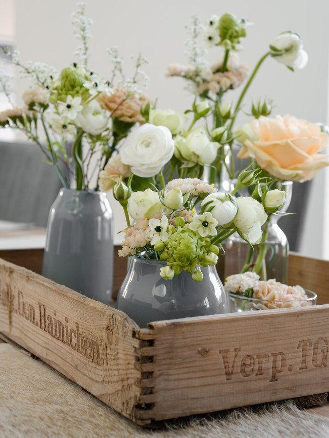 Graue Vasen mit farbenfrohen Blumensträußen. Shoppe Bikinis in Grau-/Pastelltönen