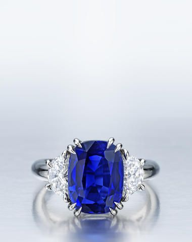 An important Kashmir sapphire and diamond ring set with an oval-cut sapphire, weight 5.23 carats, flanked by half-moon-cut diamonds; mounted in platinum; size 6. (=)