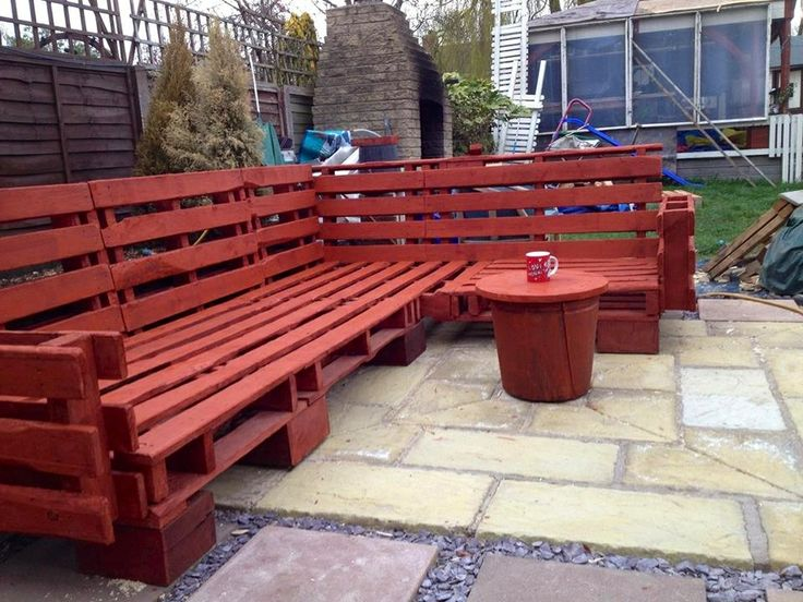 Wrap around patio seating bench. Made from pallet wood. Stained redwood color.