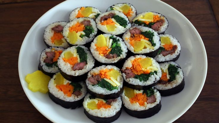 How to make gimbap (aka kimbap: 김밥) (5 rolls) 5 sheets of gim (seaweed paper) 4 cups cooked rice  ½ pound beef skirt steak (or tenderloin, or ground beef) 1 large carrot, cut into matchsticks (about 1 ½ cup) 5 strips of yellow pickled radish (use pre-cut danmuji or cut into 8 inch long strips) 8-10 ounces spinach 3 eggs 3 garlic cloves 2 teaspoons soy sauce 1 tbspn + 1 tspn brown (or white) sugar 1½ teaspoon salt 2½ tablespoons sesame oil vegetable oil