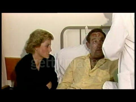 July 08, 1988: Piper Alpha disaster: Prince and Princess of Wales and Thatcher visit survivors in Aberdeen Royal Infirmary, Aberdeen, Scotland. Prince and Princess of of Wales visit badly burned survivor of Piper Alpha disaster lying in bed - Diana sits next to him. Crowd of people behind barriers. Prince and Princess of Wales chatting to rescue workers. Video.