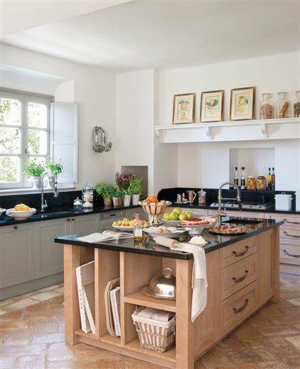 Cocina con isla de madera de roble  Encimera de granito negro. Mobiliario, realizado por Carpintería Montes. Campana extractora de obra.
