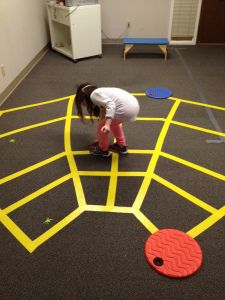 This spider web activity may be used to help children practice motor skills such as balance, ideation, motor planning, and execution. Children must walk around the spider web staying on the lines and pick up the bugs that got caught in the spider's web.