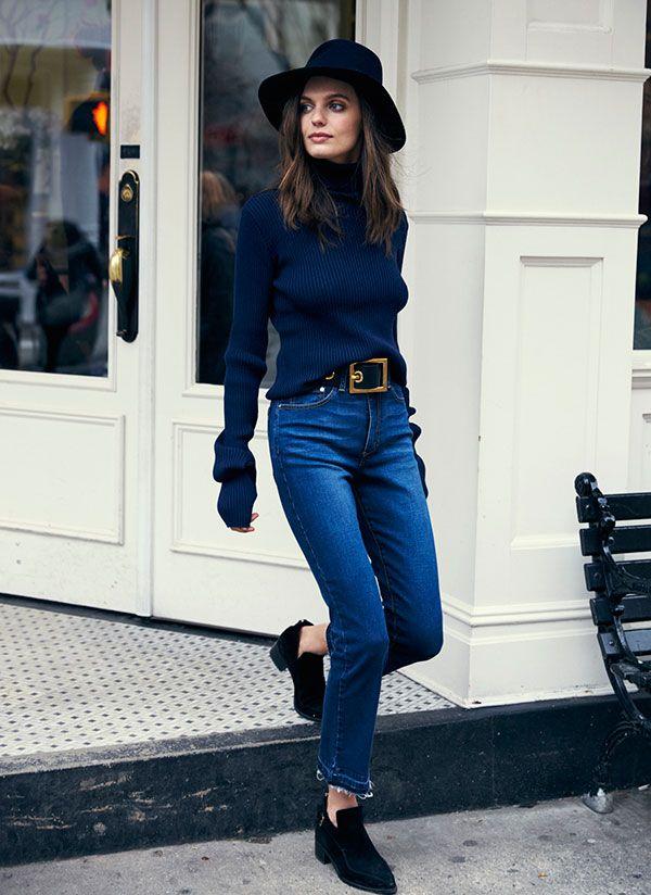 Mulher desce escadaria usando calça jeans de cintura alta cropped flare com tomboy shoes preto, turtleneck azul marinho e chapéu preto