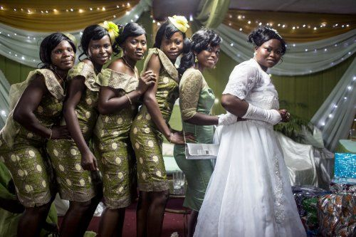 Bride Temitope Caulker poses with her bridesmaids, who, in typical Nigerian fashion, wear outfits that match the decor of the wedding hall. The wedding industry in petrol-rich Nigeria is big business. Glenna Gordon