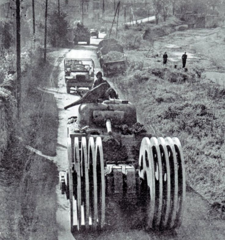 A Sherman of 6 Armoured Division, equipped with mine rollers huge, T1E3, leading a column of vehicles by Nancy on October 7, 1944.