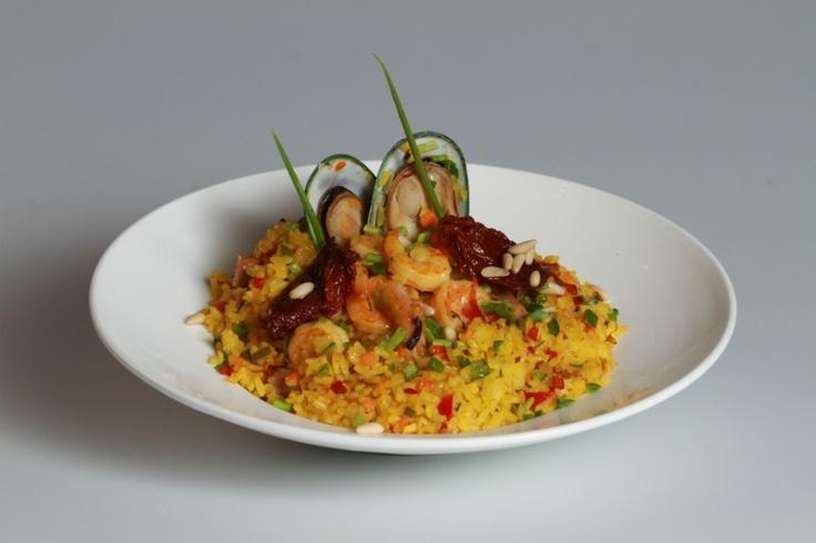 Arroz parbolizado cocido con azafrán español y vino blanco, con camarones y mejillones.
