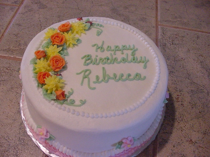 Cute round buttercream birthday cake with buttercream flowers and pearls.