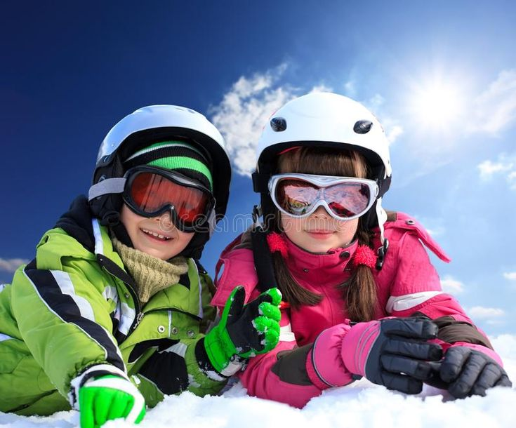 Children in ski clothing. Portrait of young boy and girl in ski clothing on snow…