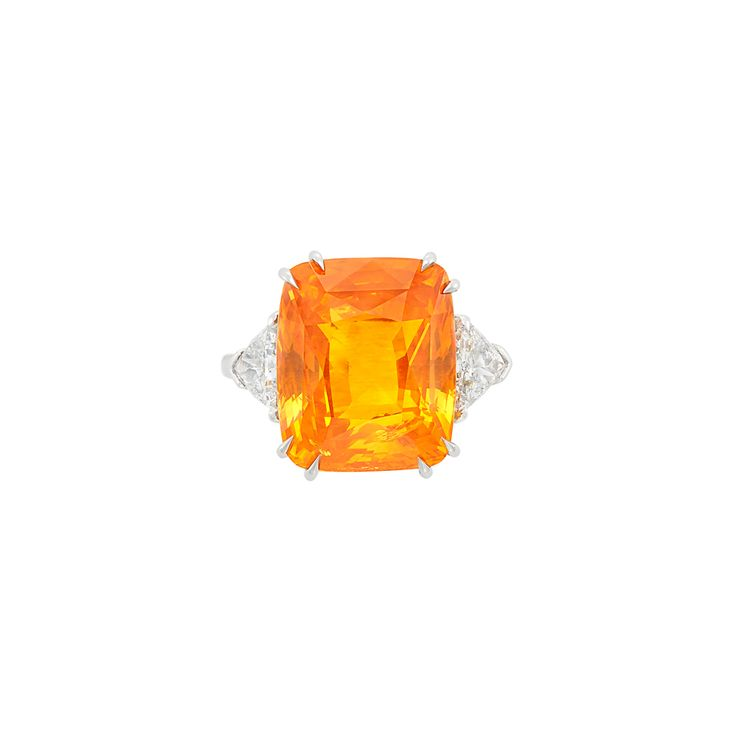 Platinum, Orange Sapphire and Diamond Ring One cushion-cut orange sapphire ap. 18.80 cts., 2 trilliant-cut diamonds ap. 1.40 cts., ap. 6.5 dwts. Size 7 1/2.