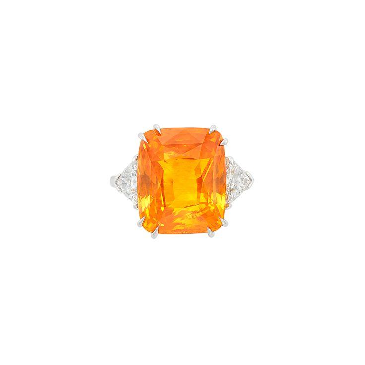 Platinum, Orange Sapphire and Diamond Ring One cushion-cut orange sapphire ap. 18.80 cts., 2 trilliant-cut diamonds ap. 1.40 cts., ap. 6.5 dwts. Size 7 1/2.