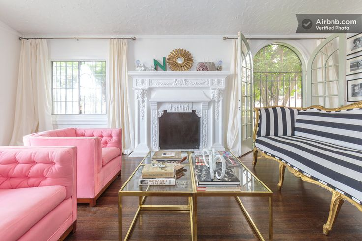 A 1920s cottage living room in LA features a navy striped couch, pink club chairs, and gold accents.