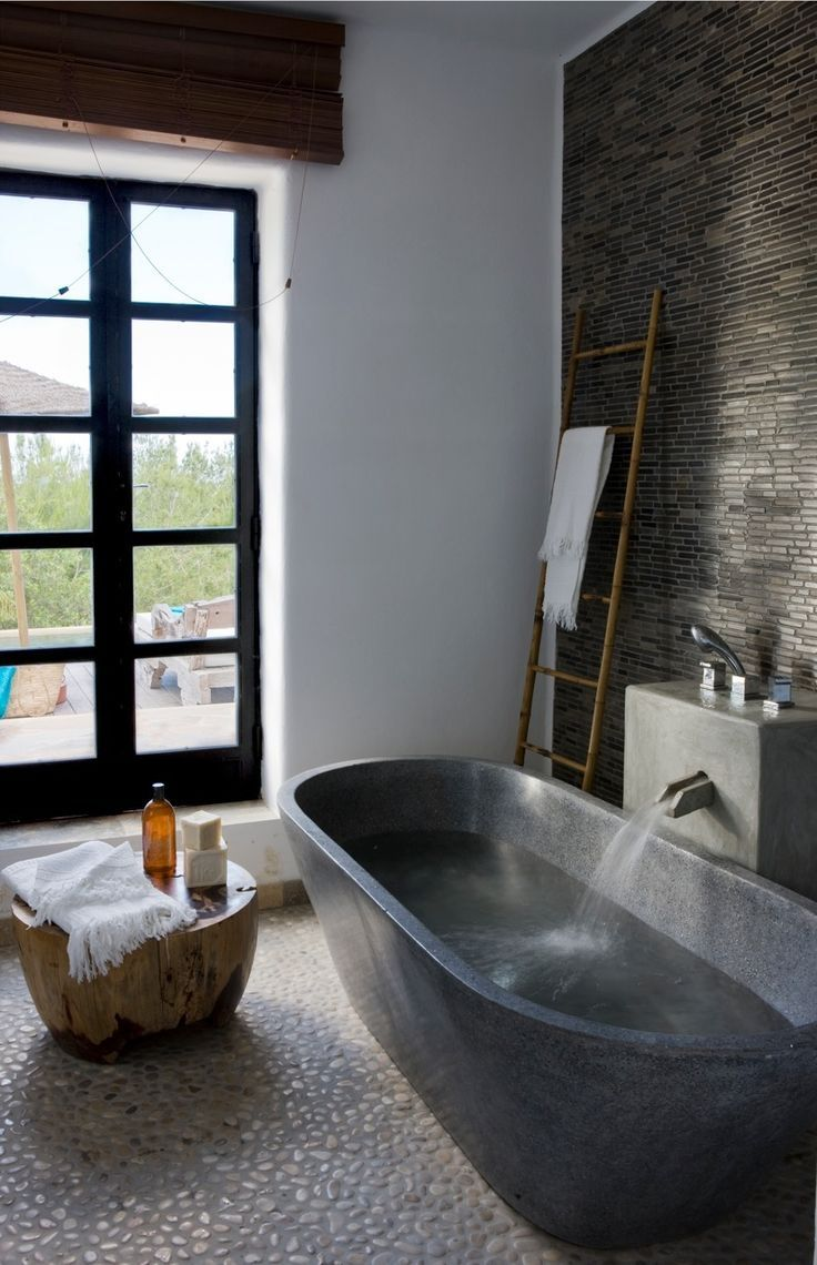 This mix of stone tile gives this bathroom a zen feeling. Grey Pencil Stone tile on the wall and polished white pebble tile on the floor. Gorgeous!!