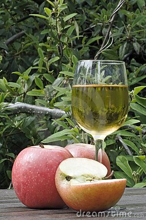 A glass of apple juice  and apples, on a wooden table outdoors