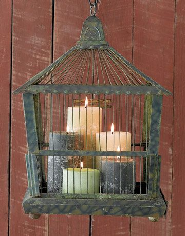 Repurposed Birdcage - A vintage metal bird cage is suspended on a chain. Large pillar candles are placed within. For saftey ensure that a heat proof candle plate is placed beneath candles, as well as the candles are distributed properly, and the cage not too close to anything flammable.