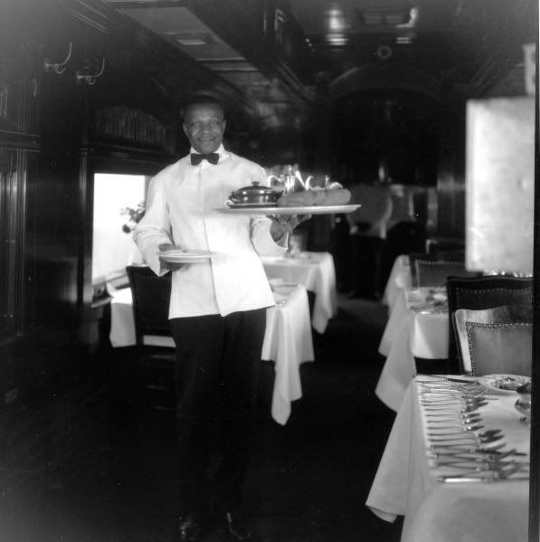 "A waiter delivers one of the N.P.'s famous ""Great Big Baked Potato"" to one of their patrons inside our 1910 Northern Pacific Dining car. This particular photo was taken around 1915 and was used as part of a promotional ad for the railroad. Pullman Porters and Waiters."